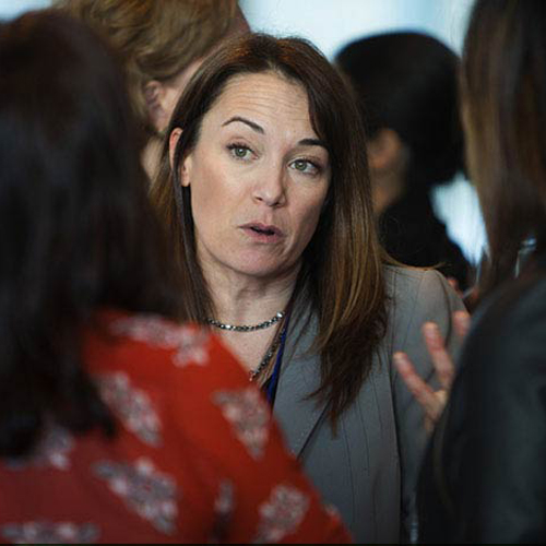 A woman conversing with other female professionals at a networking event