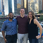 Evening-Weekend students Ashray Reddy, Connor Blankenship, and Rebekah Krikke standing smiling along the Chicago River in downtown Chicago.