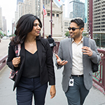 Female and male students talk while crossing the Michigan Avenue bridge in downtown Chicago.