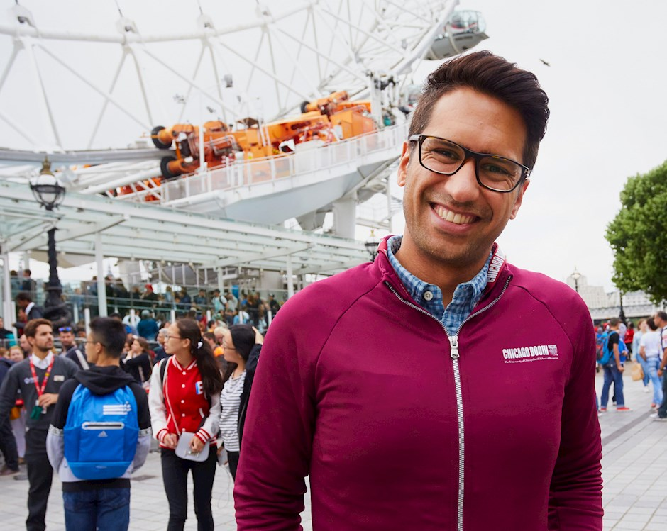 A Chicago Booth student smiles in front of the London Eye Ferris wheel