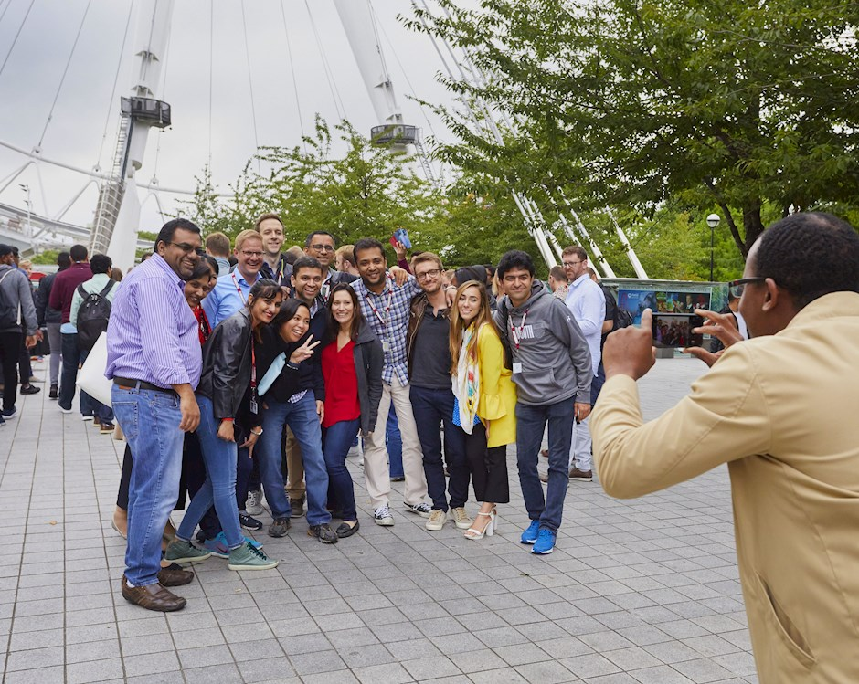 A group of Booth students pose for a photo in front of the London Eye Ferris wheel