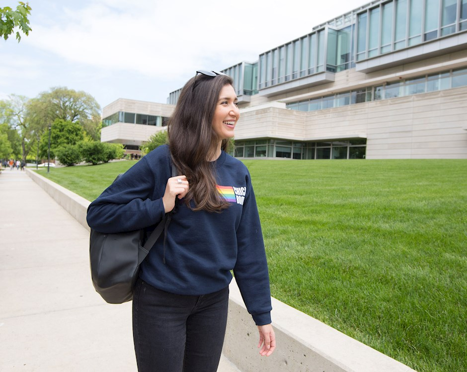 A female student walks in front of the Harper Center smiling