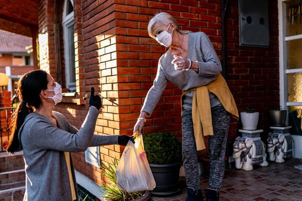 Woman with face mask delivering groceries to the front porch of elderly woman with face mask