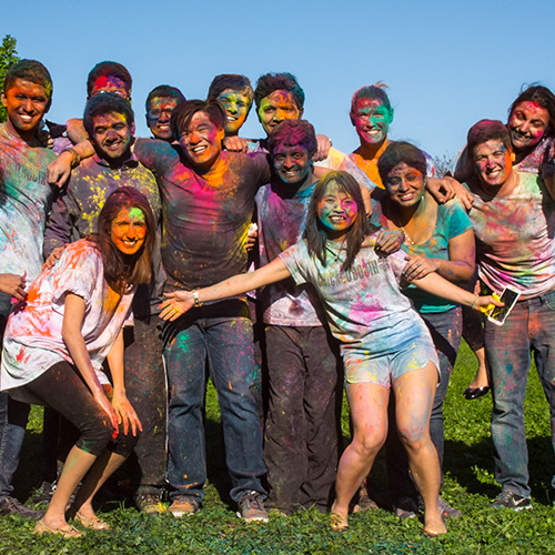 A group of students covered in multi-colored paint, following the Holi festival of colors.