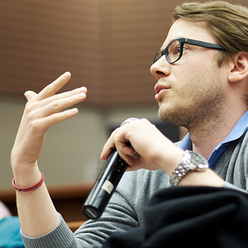 Student speaking into a microphone in a lecture hall.