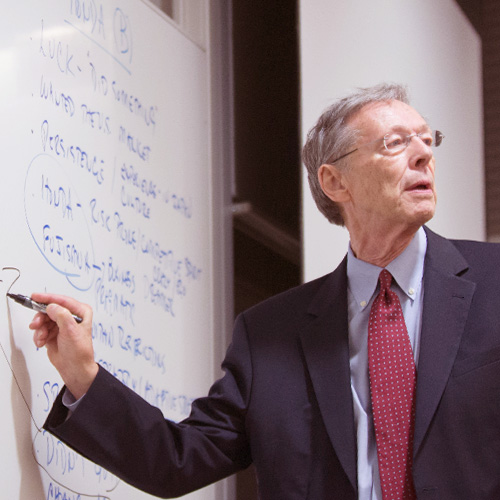 Professor at the front of class illustrating an academic concept on a whiteboard.