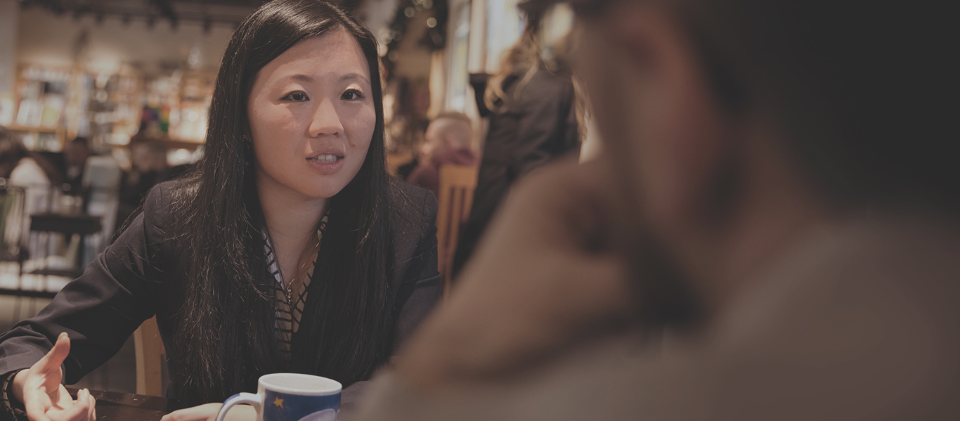 Photo of Joanne Chen in discussion with a colleague over coffee.
