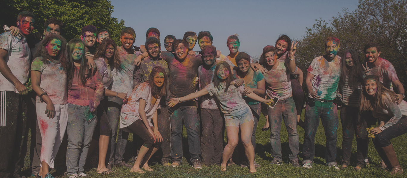 Group of students covered in multi-colored paint following a celebration of the Holi festival of colors.