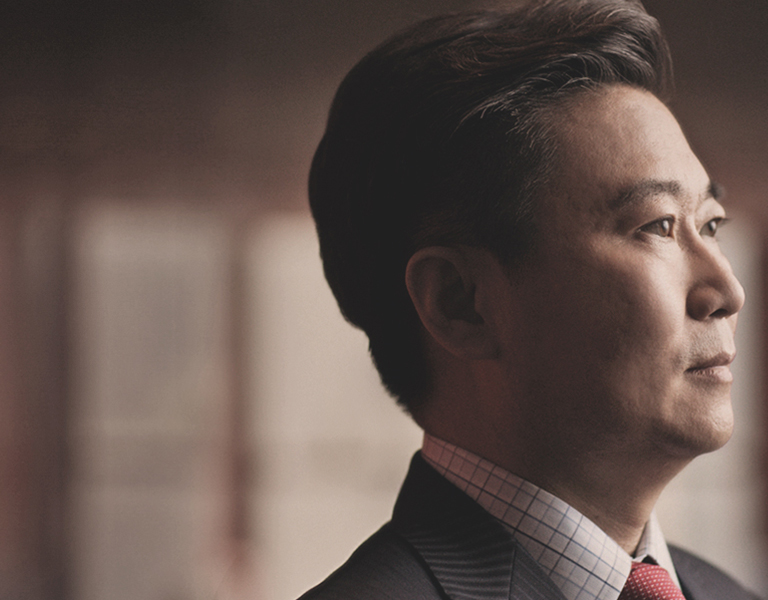 Photo of David Han, dressed in a suit, looking into the distance off-camera.