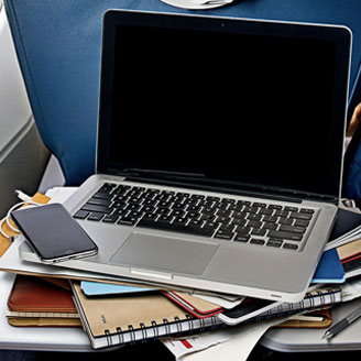 Photo of a laptop and cellphone stacked on top of notebooks in an airplane.
