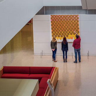 Photo of students examining and discussing an art installation at the Harper Center.