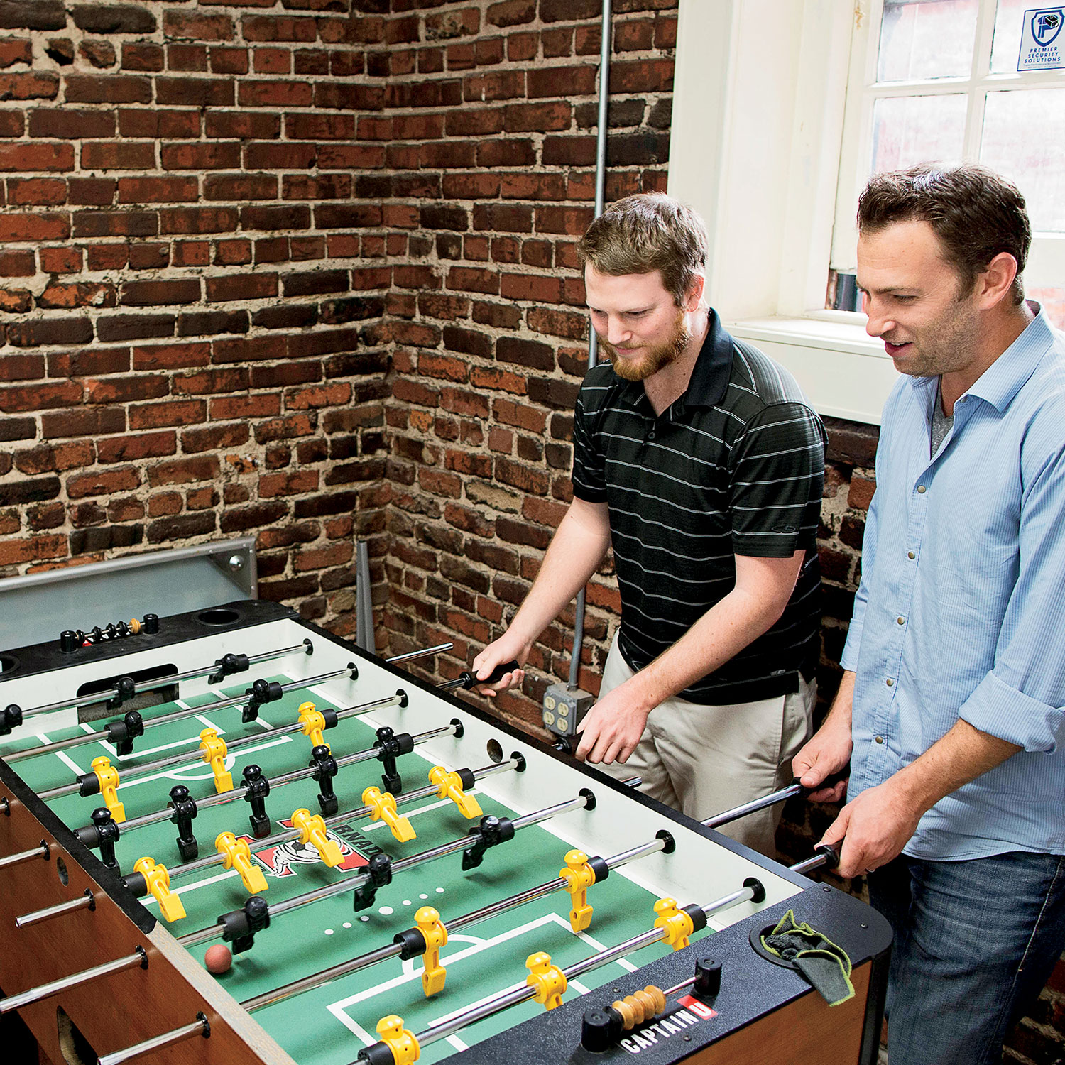 A COO Michael Farb takes a foosball break with CaptainU employees at the company's San Francisco office. Photograph by Randall Spriggs.