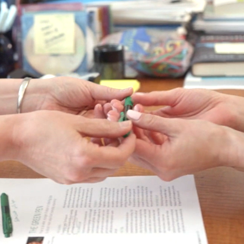 A set of hands receiving a green pen from another set of hands