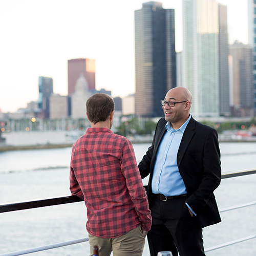 Two men talk while looking out at Chicago skyline