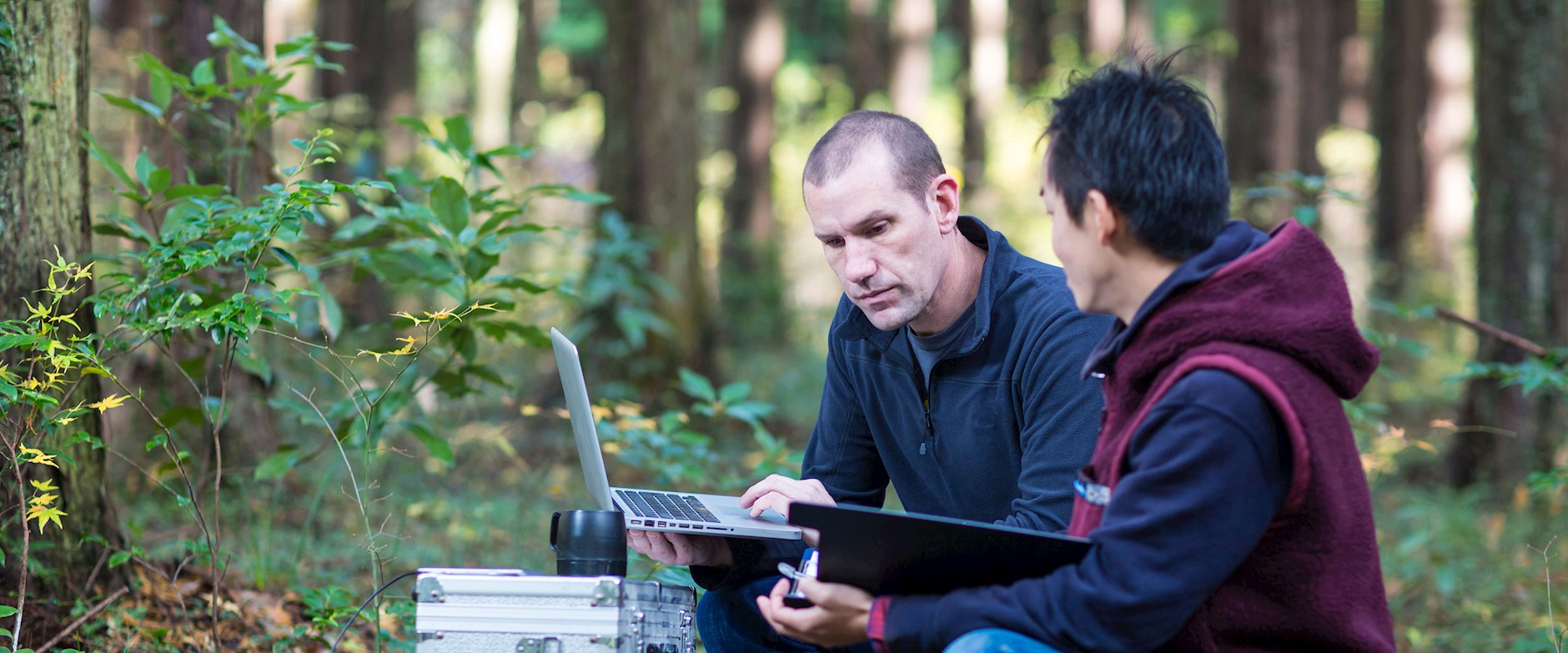 Two men working in the woods on computers