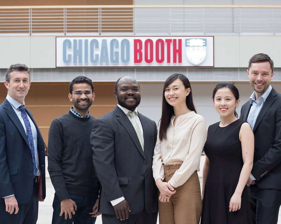 JIR 2019 alumni group standing under the Chicago Booth sign