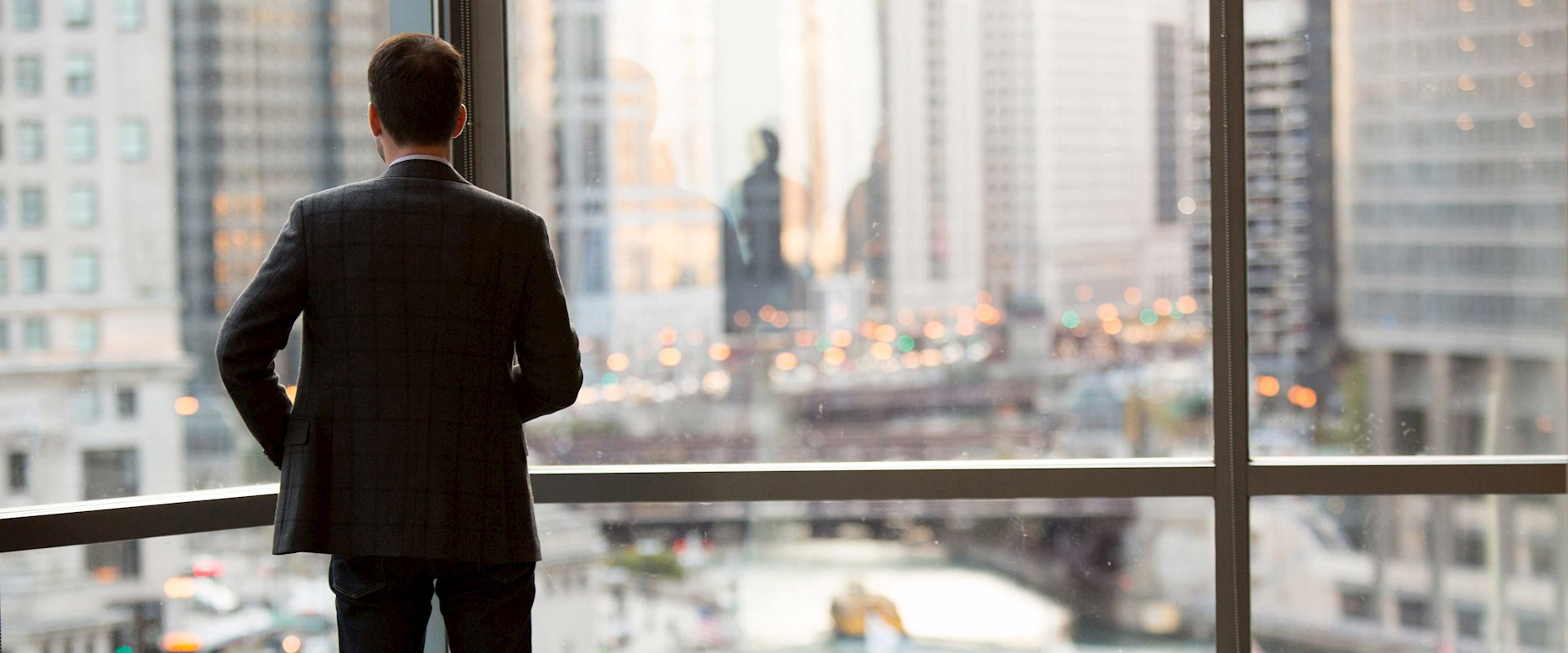 A businessman looking out the window in an urban environment
