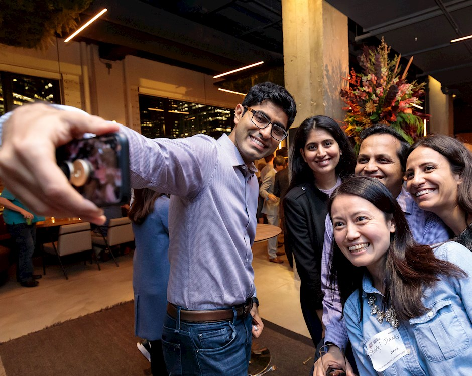 A group of alumni at a worldwide Booth event taking a group selfie