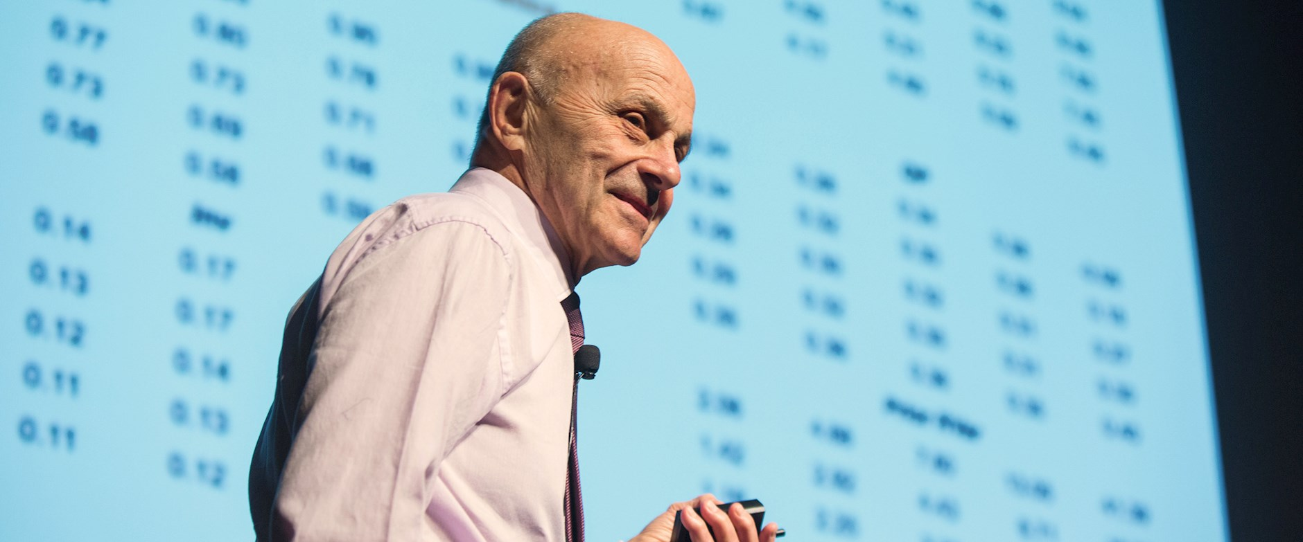 Eugene Fama presenting in front of a projector screen full on numbers