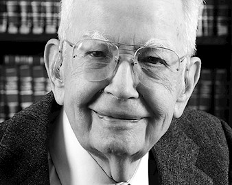 Ronald Coase headshot in front of a bookcase