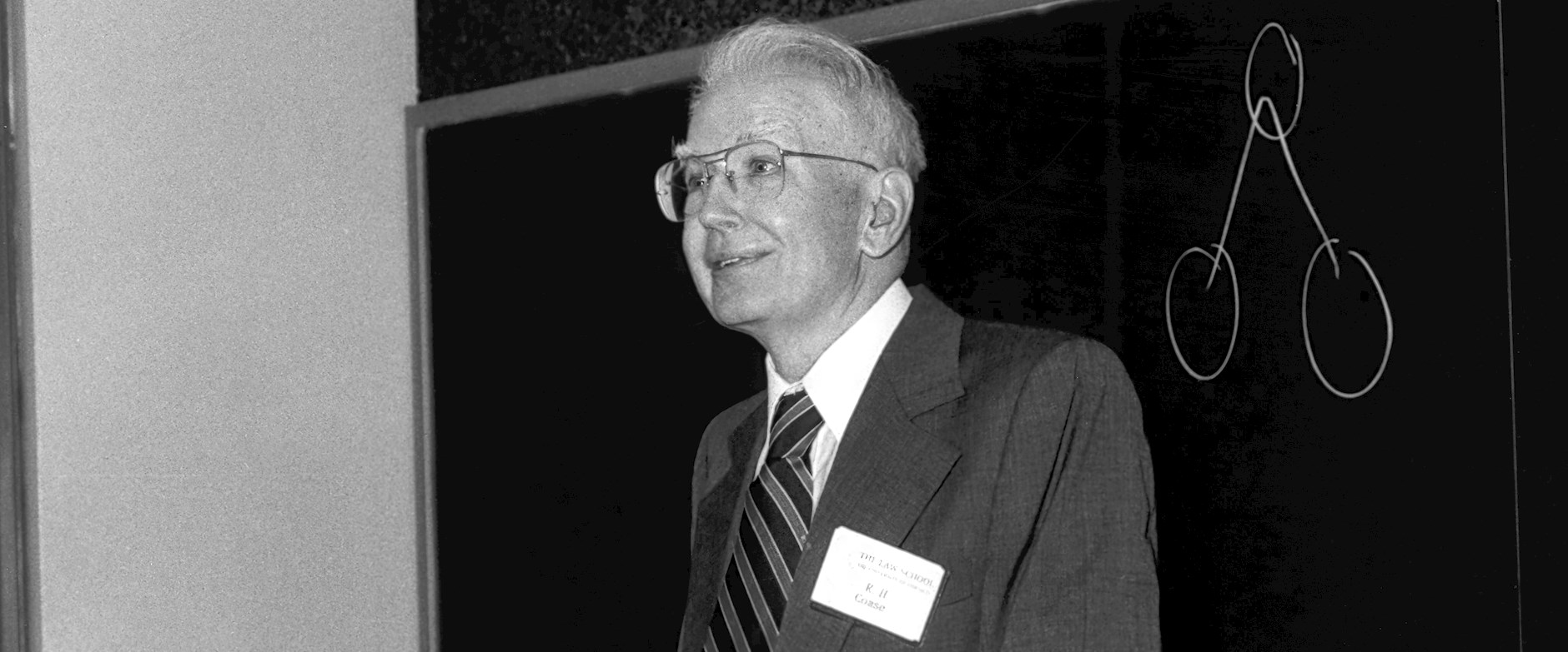 Ronald Coase standing in front of a blackboard