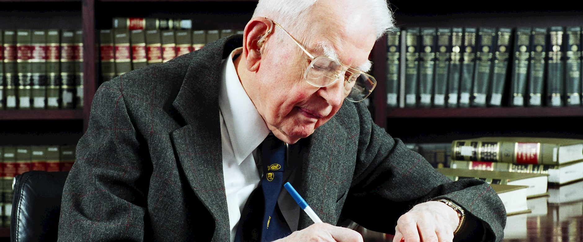 Ronald Coase writing in his office