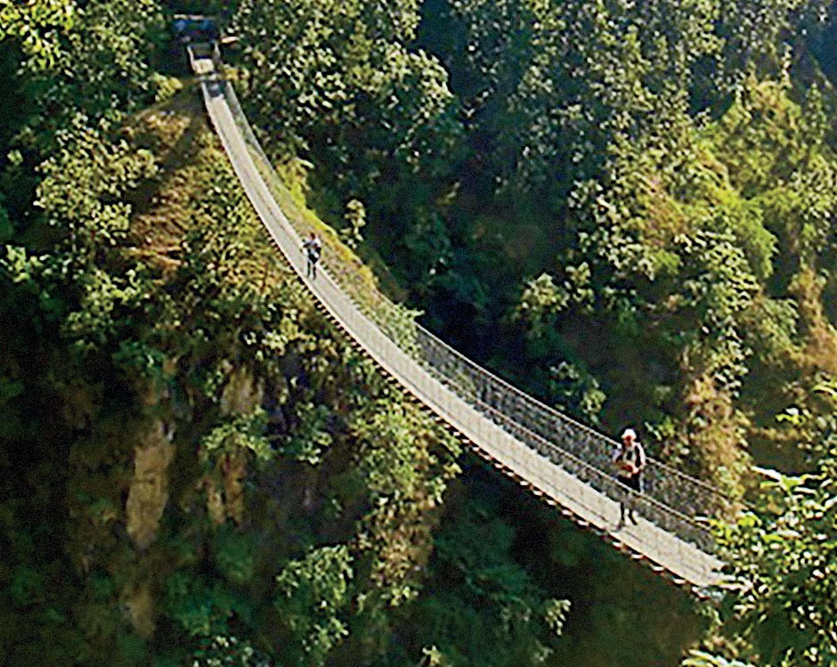 A high suspension bridge stretches over a gorge.Two people walk across the bridge.