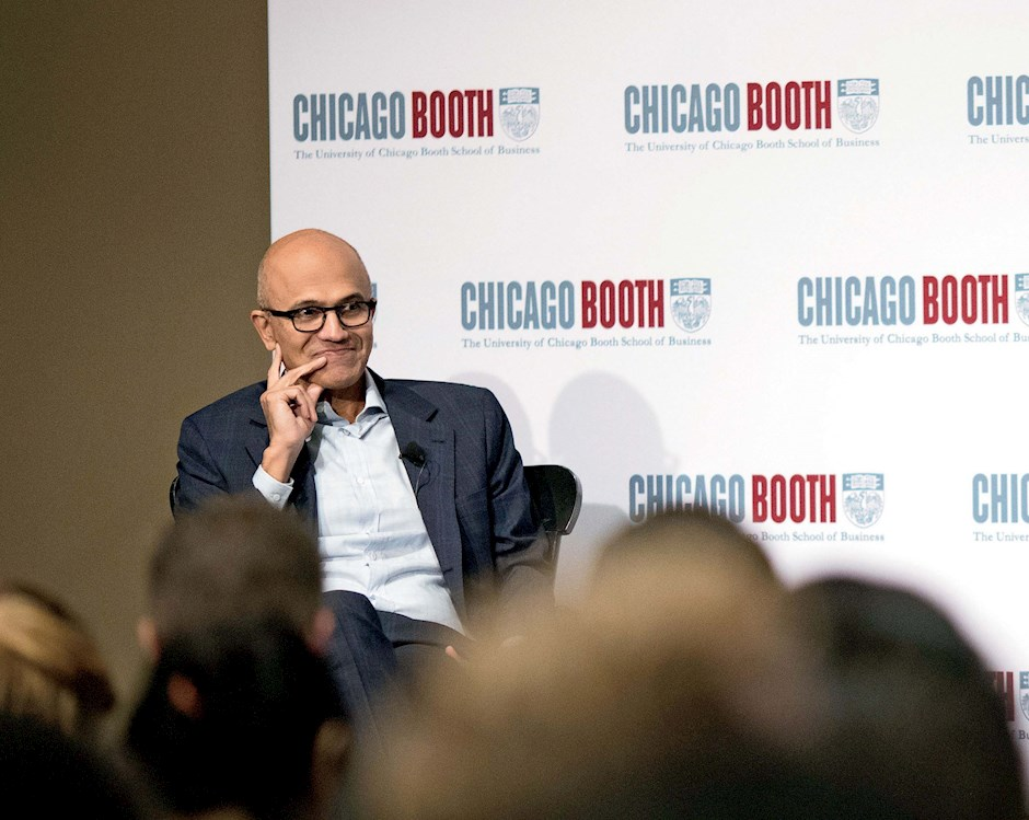 Dean Madhav Rajan seated in front of a Chicago Booth sign with Microsoft Satya Nadella