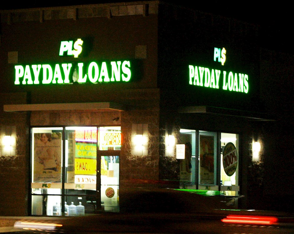 Photo of strip mall containing fast loan services such as payday loans, check cashers and title loans.