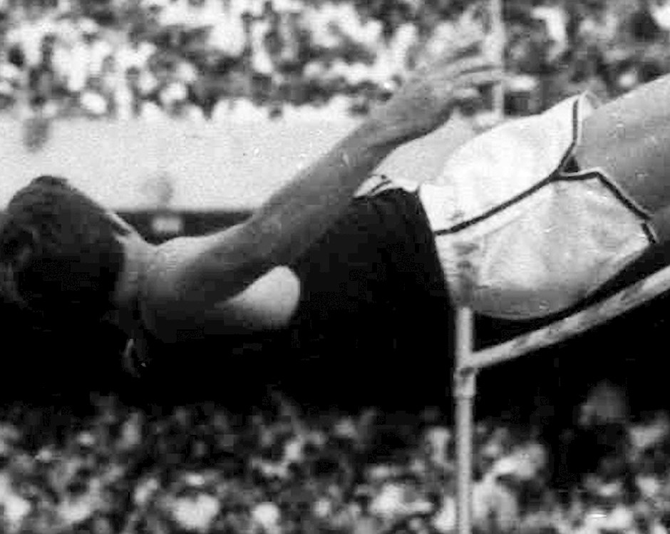 Historical photograph of an athlete soaring over the high jump at a competition.