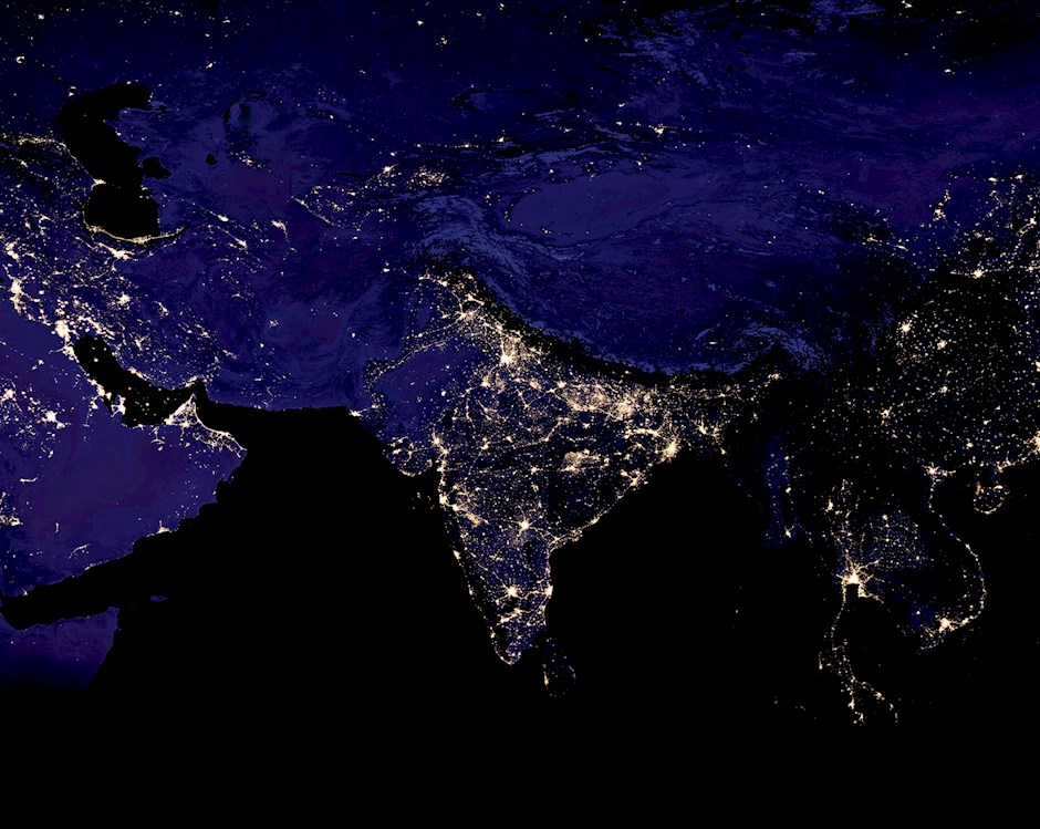 Night-time satellite of the world, flattened like a map, with lights highlighting major urban areas.