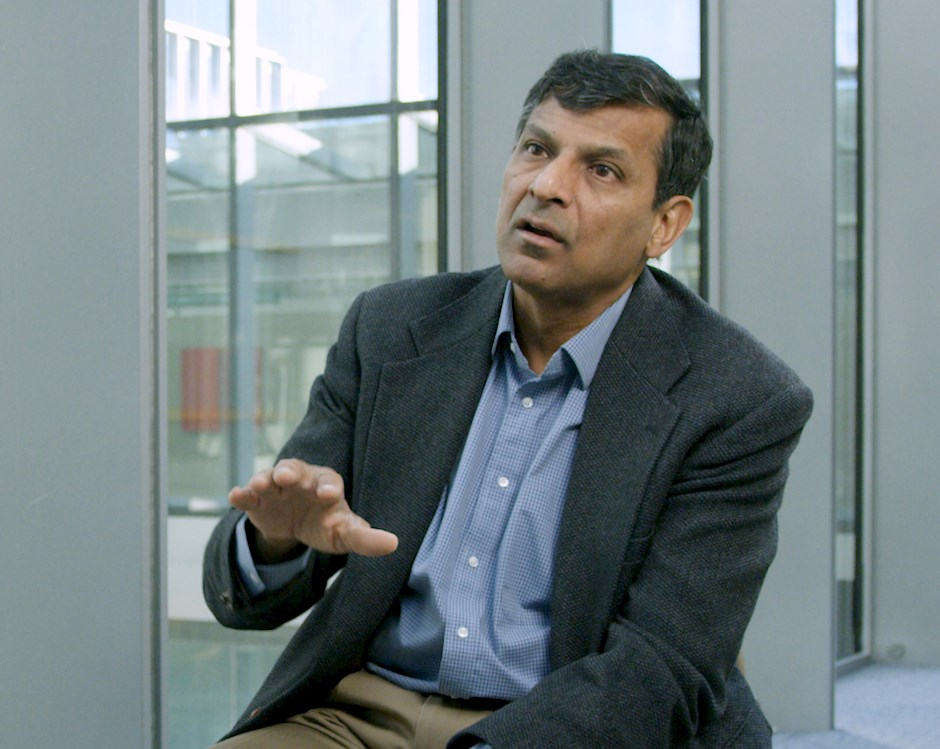 Raghuram G. Rajan sits in front of wide windows overlooking harper center and gestures while describing research.