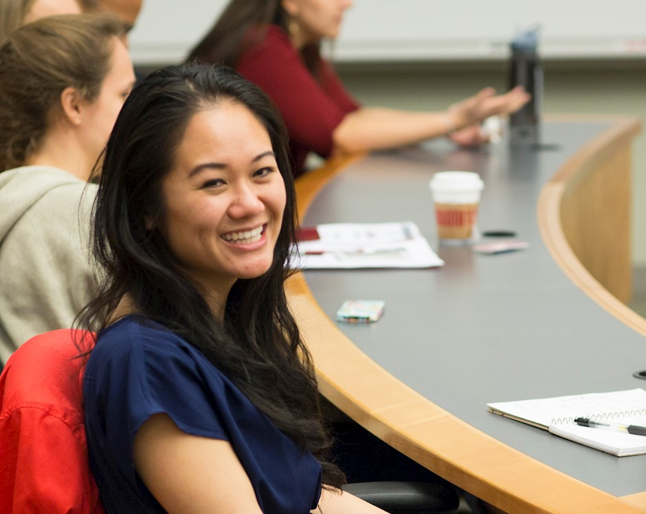 Female student smiling, engaged in class discussion