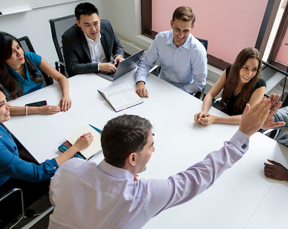Group of students meeting at a conference table, two students high fiving