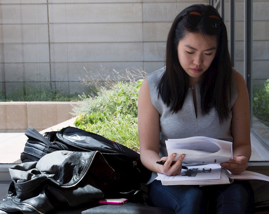 A woman looks sitting on a bench, looks at a packet of paper with a look of concentration