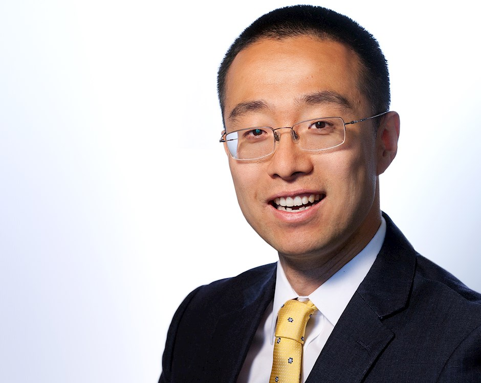 Alex Yang, a man with Asian heritage, smiles and wears a business suit with yellow tie.