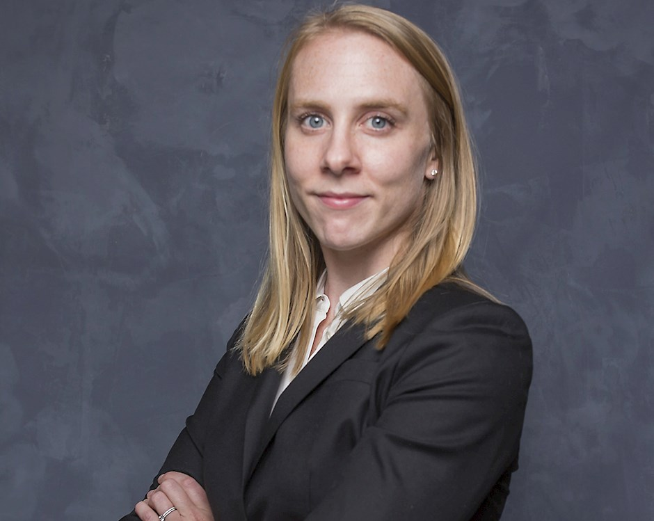 Kaitlin Woolley, a woman with shoulder-length blonde hair, stands with crossed arms in front of gray background.