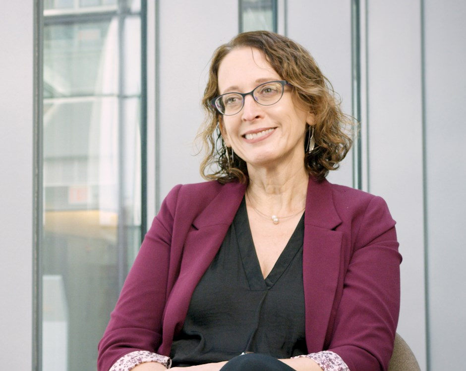Professor Ayelet Fishbach, a woman with curling shoulder-length hair, glasses and a plum-colored suit jacket, sitting in front of wall of windows.