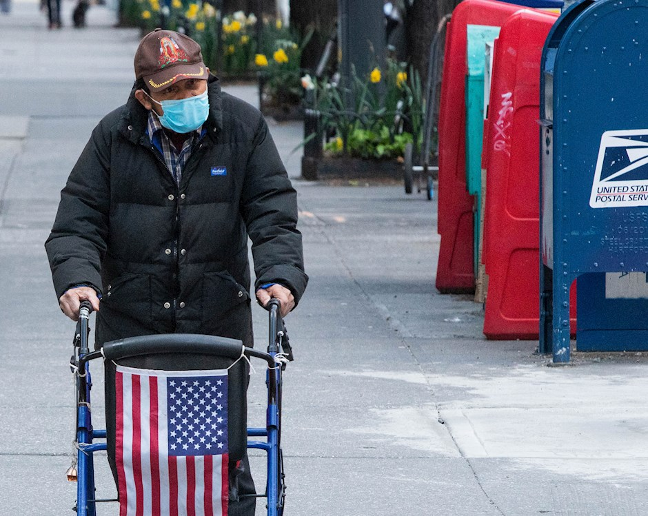 Person wearing a mask using a walker draped with an Anerican flag walking down the street