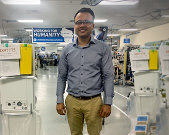 Chandan Singh standing in front of a hallway of ventilators at GE